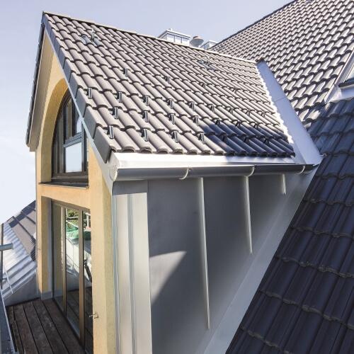Hausdach mit Roofinox Edelstahl Verblechung zum Schutz vor Wasser. Verblechung für Übergänge von Dach und Dachrinne, am Dachrand, Umfassung von Fenstern und Türen und im Sockelbereich.